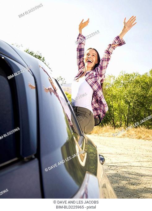 Hispanic woman wearing plaid shirt sitting on car celebrating