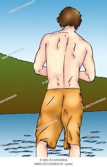 Back side of man in shorts wading in the water