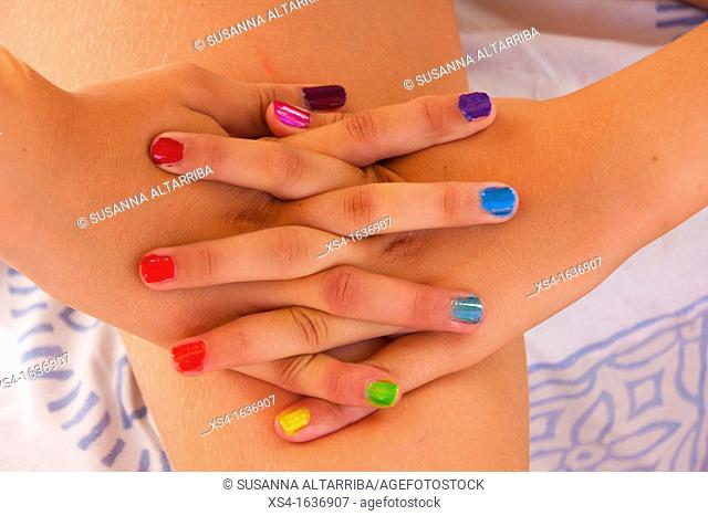 Hands of young girl with colors nails