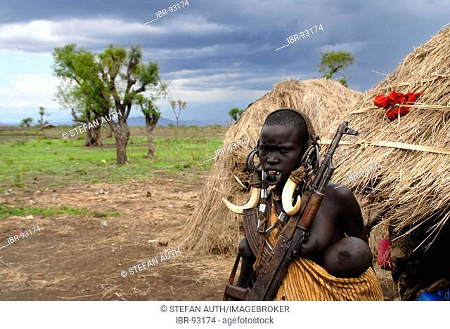 Woman of the Mursi people wearing head decoration of animal teeth Kalaschnikow and a baby in front of her hut Ethiopia