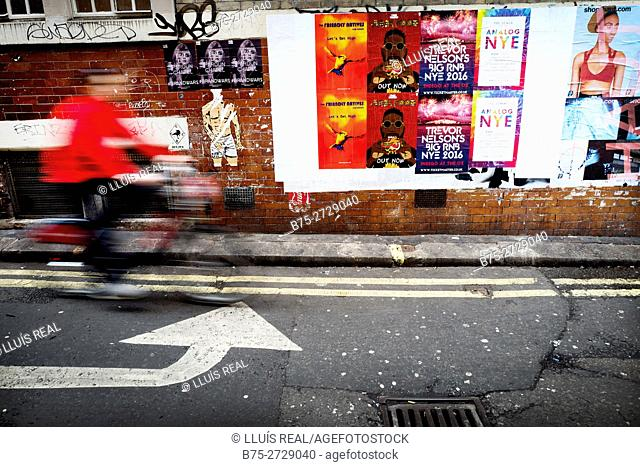 Street scene showing a wall with different advertising posters, unrecognizable man riding a bicycle  and left turn arrow sign on the pavement