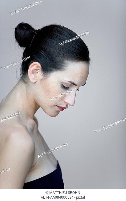 Young woman in profile, looking down, portrait