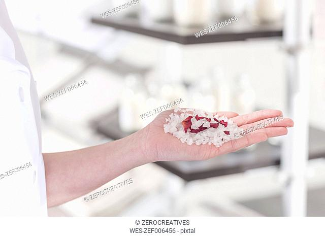 Shop assistant in wellness shop with beauty product in hand