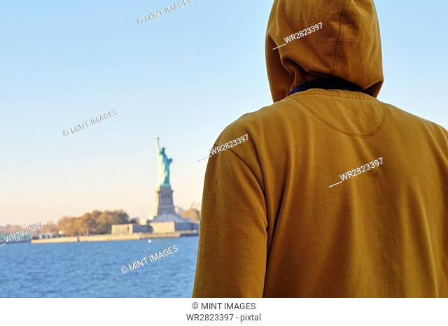 One person in a sweatshirt with hood up looking at the Statue of Liberty on Liberty Island in New York Harbor