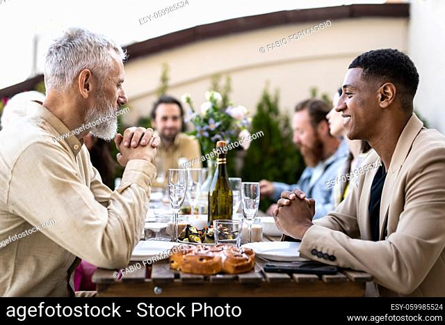 Storytelling footage of a multiethnic group of people dining on a rooftop. Family and friends make a reunion at home