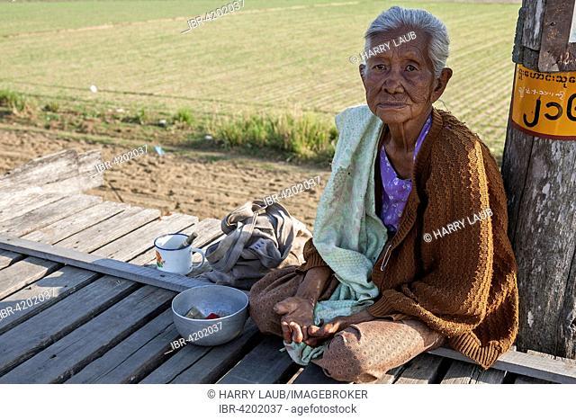 Native leper woman sitting on the U Bein Bridge, begging, Amarapura, Division Mandalay, Myanmar