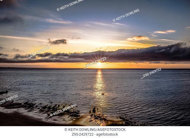 Sun over the horizon on the Irish sea off Banginbun strand on the Wexford coast, Southern Ireland