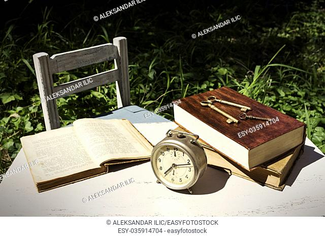 Vintage still life with old alarm clock, keys and books on a white wooden table