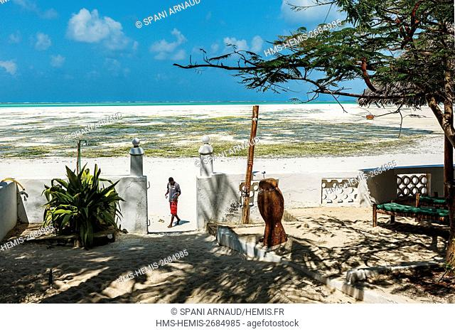 Tanzania, Zanzibar, Jambiani, man past the waterfront of a luxury hotel on the beach at low tide