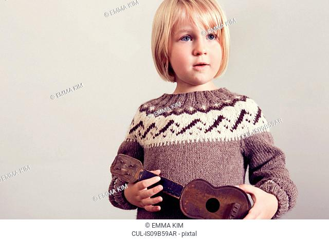 Girl holding old wooden toy guitar