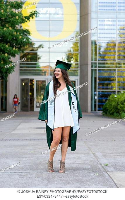 EUGENE, OR - MAY 23, 2017: Female college student posing for graduation photos in the Lillis Business Plaza on campus at the University of Oregon in Eugene