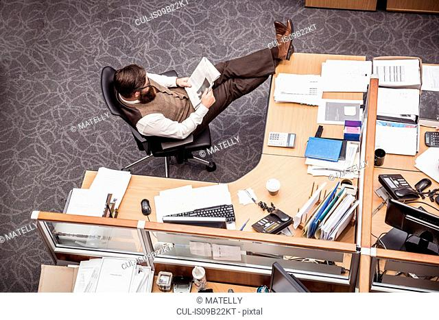 Overhead view of businessman with feet up on office desk