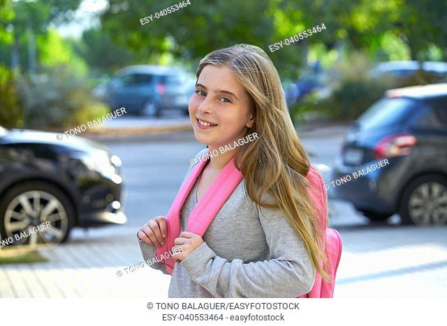 Blond kid student girl with backpack in the city back to school