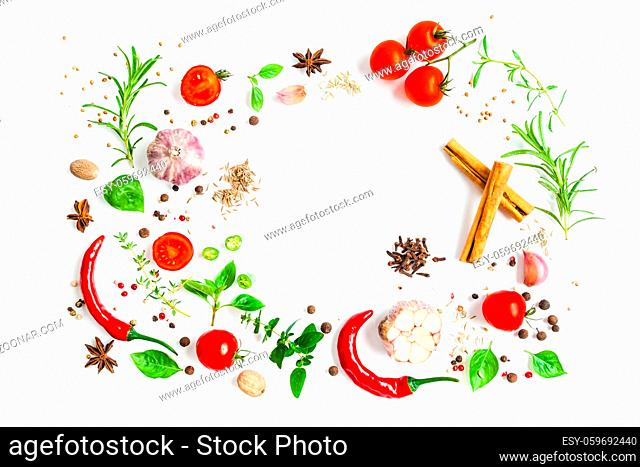 Food frame isolated on white. Tomatoes and chili peppers with herbs and spice scattered on the table. Top view