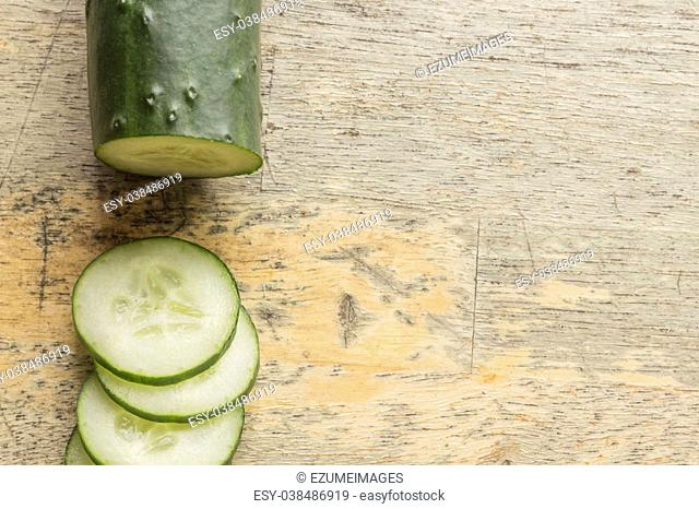 Fresh organic cucumber chopped on distressed table top