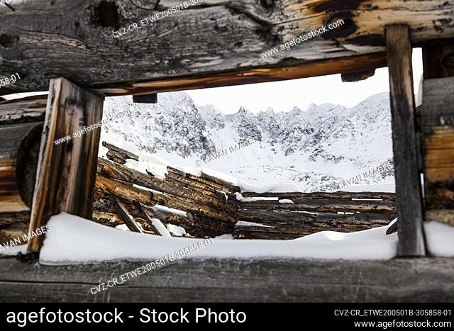 Jagged mountains and log cabin ruin in Mayflower Gulch, Colorado