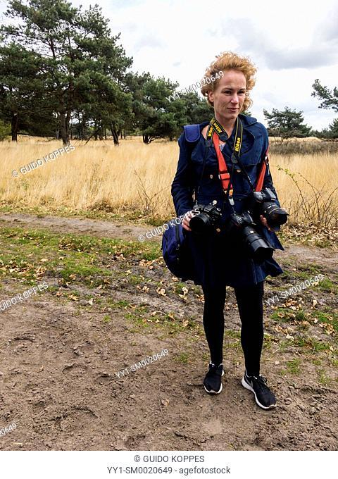 Regte Heide, Riel, Netherlands. Female redheaded photographer wearing three, heavy dslr camera's