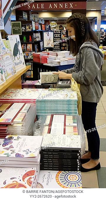Preteen Girl Browsing in Book Store, Rochester, New York, USA