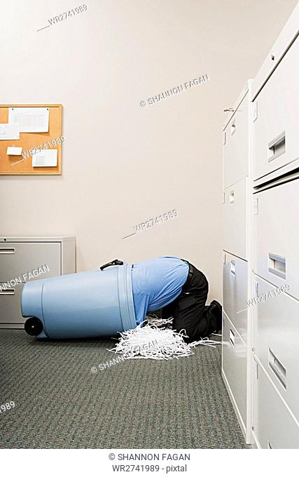 Man in shredded paper bin