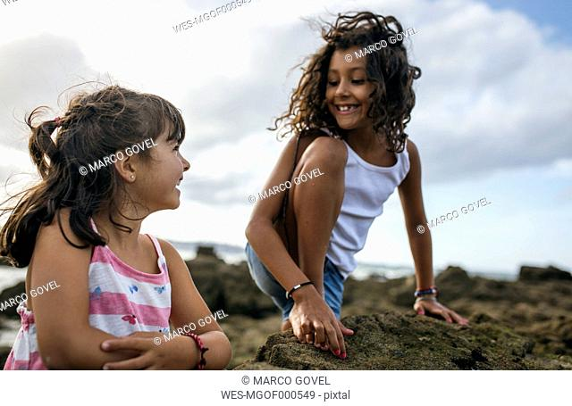 Spain, Gijon, portrait of two smiling little girls playing at rocky coast