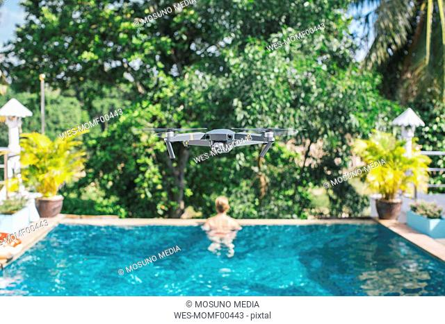 Flying drone over the swimming pool, woman in the background