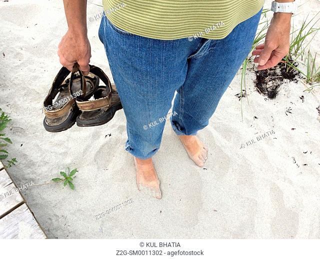 Woman standing on white sand, sandals in hand, Nova Scotia, Canada