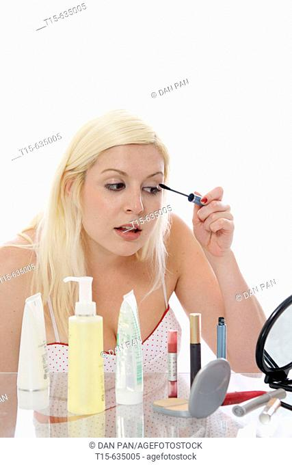 Young woman putting on makeup, eye lashes