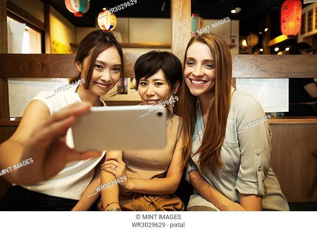 Three women sitting side by side in a restaurant, taking selfie with smartphone