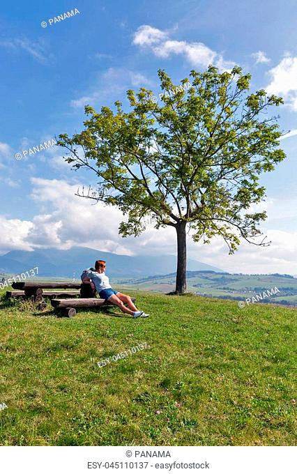 Caucasian middle aged woman hiker have a rest on wooden bench. Summer hills landscape close to Liptovsky Trnovec village in Slovakia