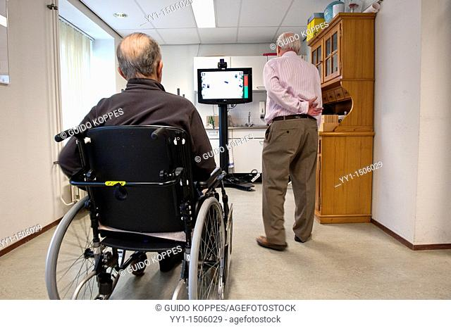 Rotterdam, Netherlands. A senior adult male rehabilitating inside a nursing home ward, after suffering a stroke, causing parts of his body to be paralyzed