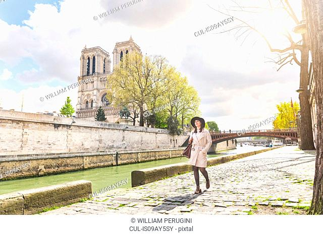 Stylish young woman strolling along riverside at Notre Dame, Paris, France