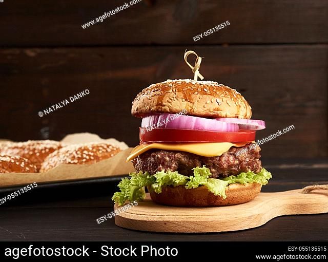 cheeseburger with tomatoes, barbecue cutlet and sesame bun on an old wooden cutting board, brown background. Fast food