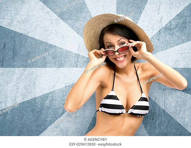 Half-length portrait of female wearing bikini, hat and sunglasses, on striped background. Concept of summer holidays and traveling