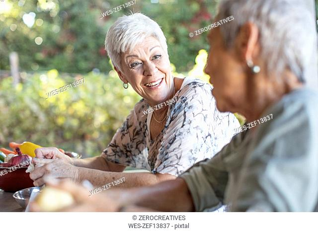Portrait of smiling senior woman listening to her friend on terrace while preparing lunch