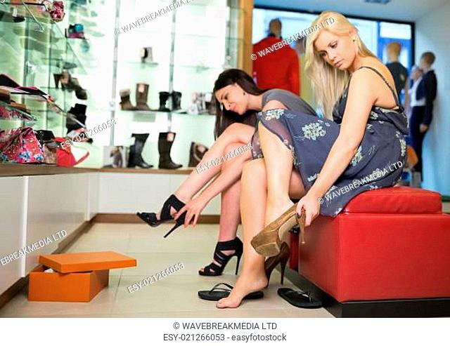 Women sitting trying on shoes