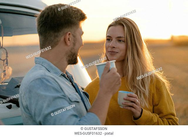 Smiling young couple holding mugs at camper van in rural landscape