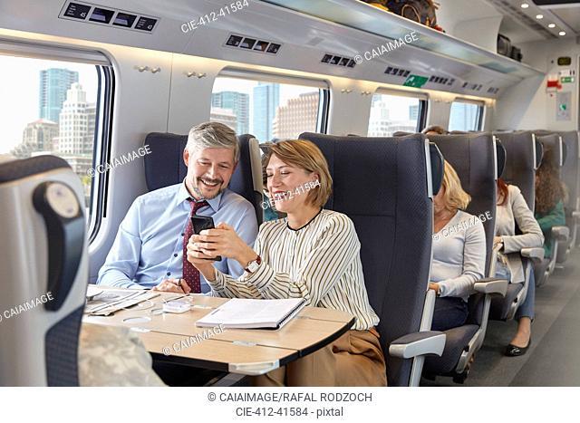 Businessman and businesswoman using smart phone on passenger train