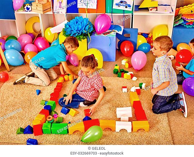 Group children male and female game blocks on floor in kindergarten . Top view