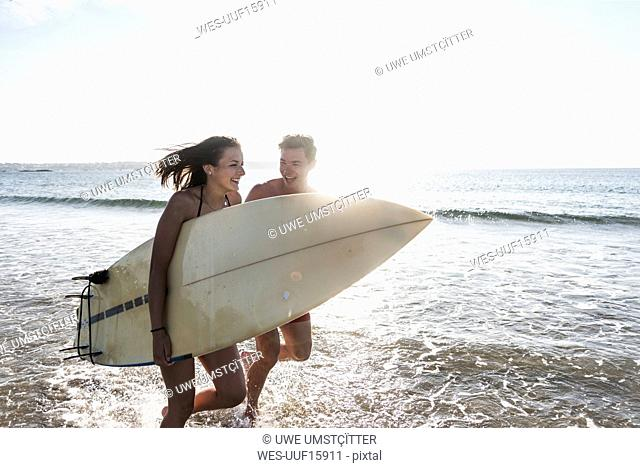France, Brittany, happy young couple with surfboard running in the sea