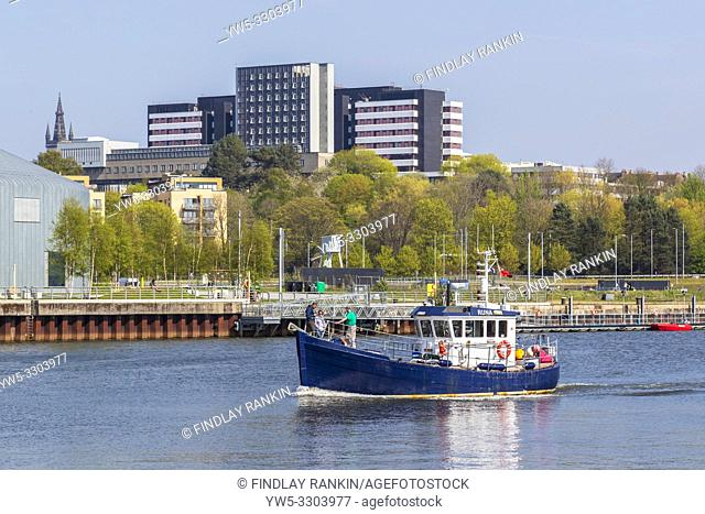 Small fishing boat sailing along the River Clyde near Anderston, Glasgow, UK