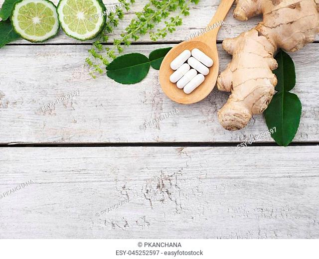 herbal pills in wooden spoon with ginger root, Kaffir lime fruit and basil flower on wood background with copy space. Above view