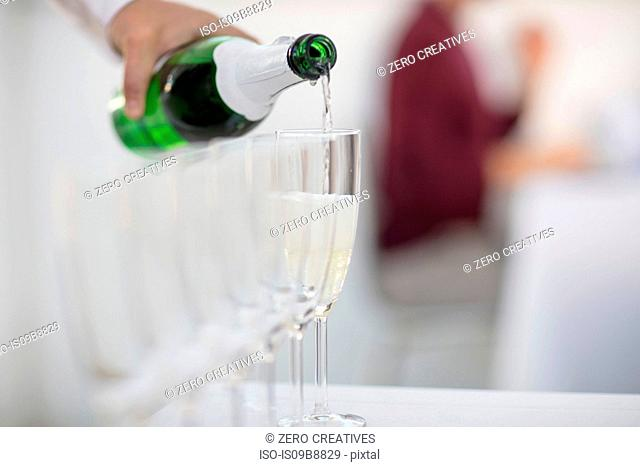 Waiter pouting champagne into champagne glasses, close-up