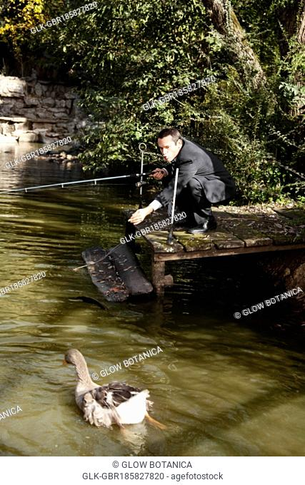 Businessman fly-fishing in a river