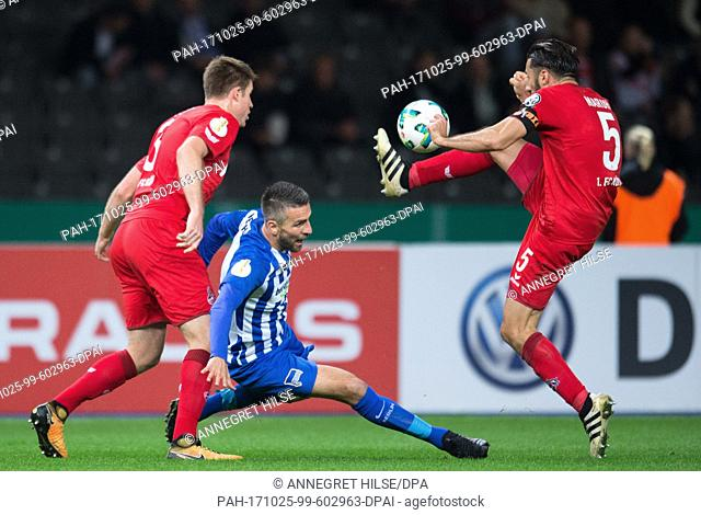 Berlin's Vedad Ibisevic falls during a three-way battle with Cologne's Dominique Heintz (L) and Dominic Maroh (R) during the DFBCup soccer match between Hertha...