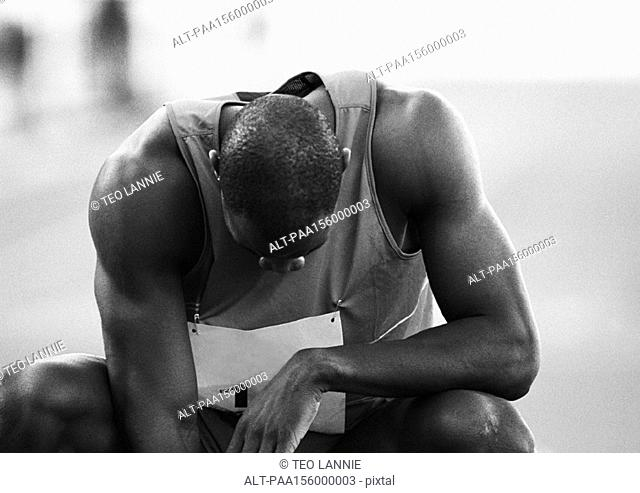 Male athlete crouching, head down, close-up, b&w