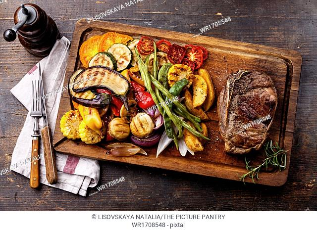 Club Beef steak and Grilled vegetables on cutting board on dark wooden background
