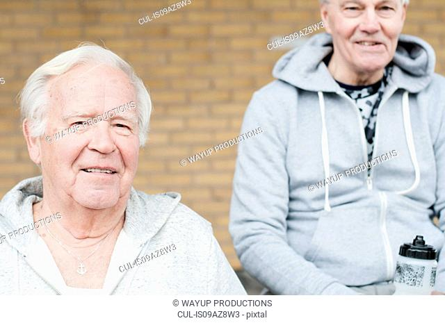 Senior friends wearing sport clothes sitting together looking at camera