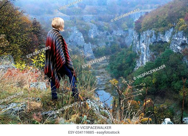 Caucasian lady stands on the edge of Emen canyon near the city of Veliko Tarnovo in Bulgaria on a raw foggy morning in the fall