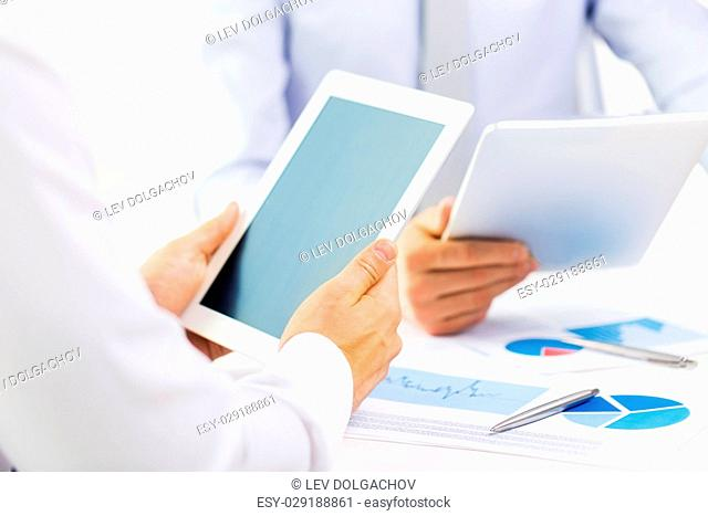 people, technology, work and corporate concept - businesswomen with tablet pc computers and charts at office