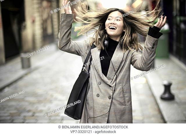 young buoyant Asian woman with windswept hairs in streets of Paris, France